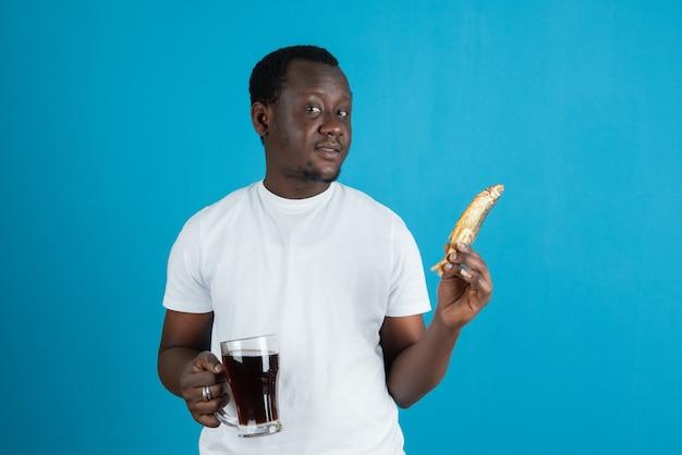 Afbeelding van een man in een wit t-shirt met gedroogde vis en een glazen mok wijn tegen een blauwe muur