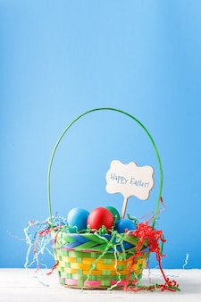 Afbeelding van een mand met kleurrijke eieren op lege blauwe muur met wens voor vrolijk pasen