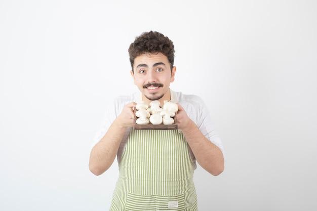 Afbeelding van een mannelijke kok die een bord met rauwe champignons op wit vasthoudt