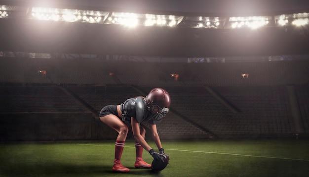 Afbeelding van een meisje in het uniform van een american football-teamspeler die zich voorbereidt om de bal in het stadion te spelen. sportconcept. gemengde media