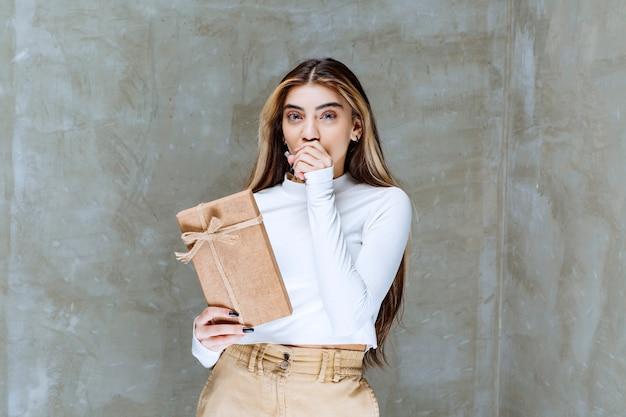 Afbeelding van een meisjesmodel dat een document over steen vasthoudt