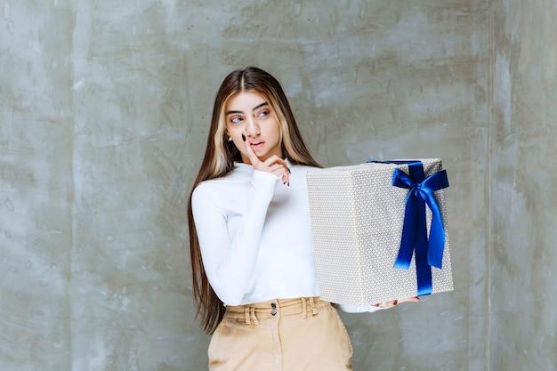 Afbeelding van een meisjesmodel dat een huidige doos met boog houdt die over steen wordt geïsoleerd