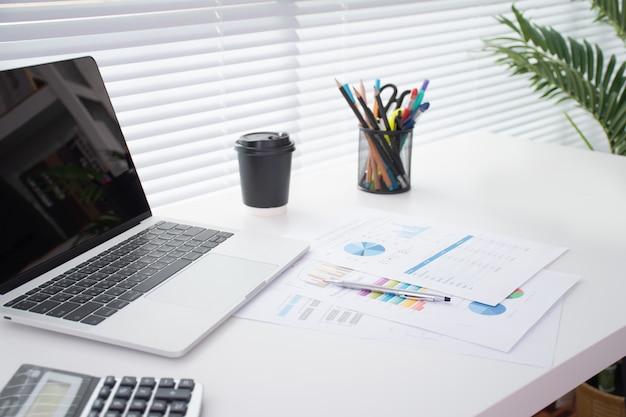 Afbeelding van een modern bureau met een laptop, een pen, een rekenmachine en een grote stapel documenten op een wit bureau in de buurt van een groot raam.