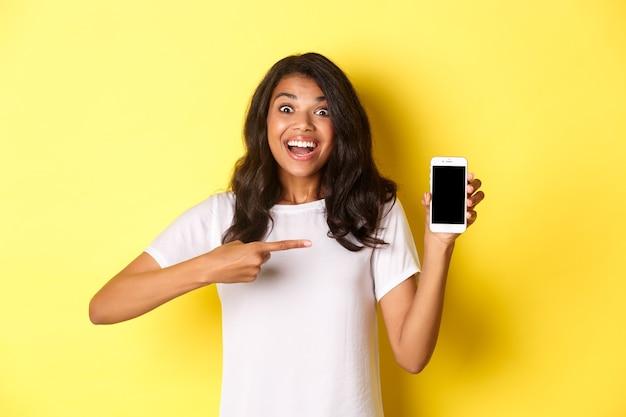 Afbeelding van een mooi afro-amerikaans meisje dat lacht en opgewonden kijkt terwijl ze naar de smartphone wijst