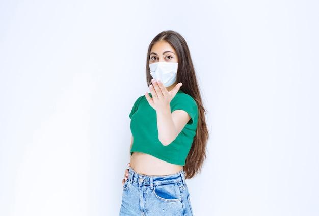 Afbeelding van een mooi jong meisje met een medisch masker dat naar de camera kijkt en poseert.