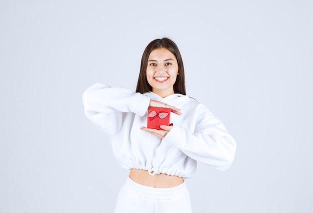 Afbeelding van een mooi jong meisjesmodel met een geschenkdoos. Gratis Foto