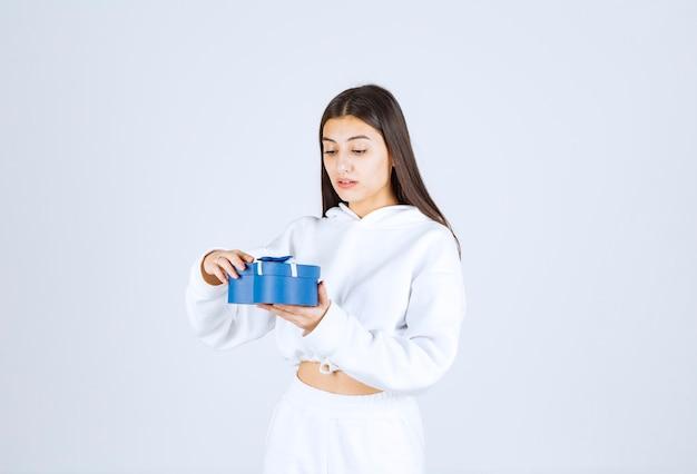 Afbeelding van een mooi jong meisjesmodel met een hartvormige geschenkdoos. Gratis Foto