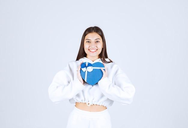 Afbeelding van een mooi jong meisjesmodel met een hartvormige geschenkdoos.