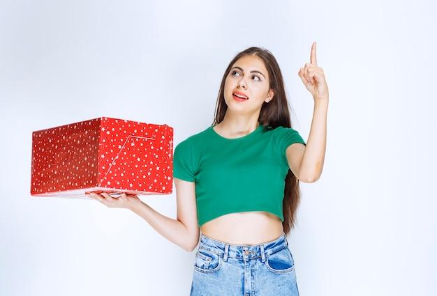 Afbeelding van een mooi meisje met een rode geschenkdoos die naar boven wijst op een witte achtergrond.