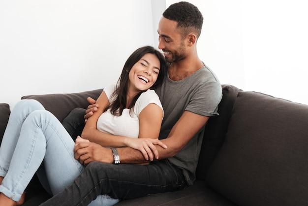Afbeelding van een mooi paar dat thuis op een bank lacht. ogen dicht.
