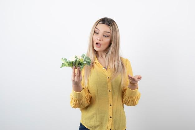 Afbeelding van een mooi vrouwenmodel dat naar bloemkool kijkt.
