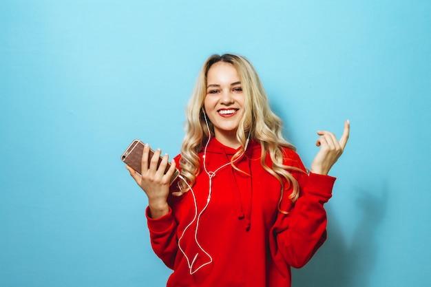 Afbeelding van een mooie blonde opgewonden vrouw luisteren naar muziek in hoofdtelefoons en dansen