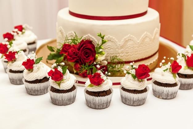 Afbeelding van een mooie bruidstaart bij huwelijksreceptie. bruidstaart met rode rozen