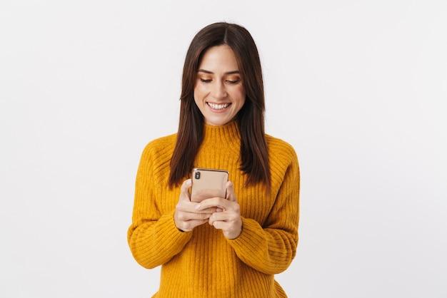 Afbeelding van een mooie brunette volwassen vrouw die een trui draagt die lacht en een mobiele telefoon vasthoudt die op wit wordt geïsoleerd