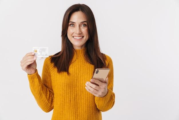 Afbeelding van een mooie brunette volwassen vrouw die een trui draagt met een mobiele telefoon en een creditcard op wit wordt geïsoleerd