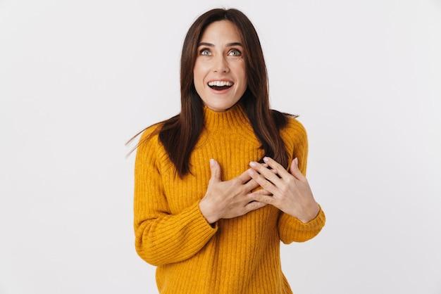 Afbeelding van een mooie brunette volwassen vrouw met een trui die lacht en omhoog kijkt naar copyspace geïsoleerd op wit