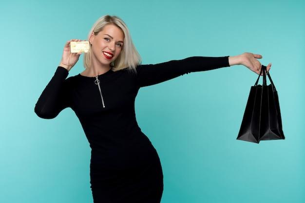 Afbeelding van een mooie gelukkige jonge blonde vrouw die zich voordeed op de blauwe muur met boodschappentassen.