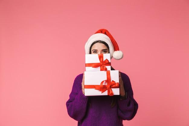 Afbeelding van een mooie gelukkige jonge emotionele vrouw poseren geïsoleerd over roze geschenkdozen met kerstmuts die gezicht bedekt.