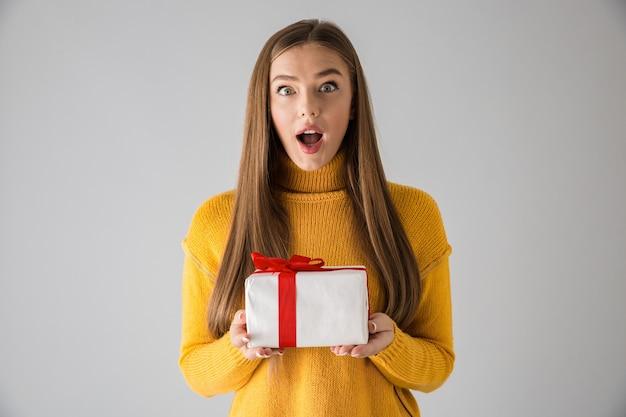 Afbeelding van een mooie geschokt gelukkige jonge vrouw geïsoleerd over grijze muur met geschenkdoos aanwezig.