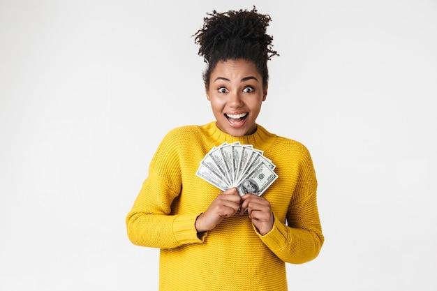 Afbeelding van een mooie jonge afrikaanse opgewonden emotionele gelukkige vrouw die zich voordeed op een witte muur met geld.