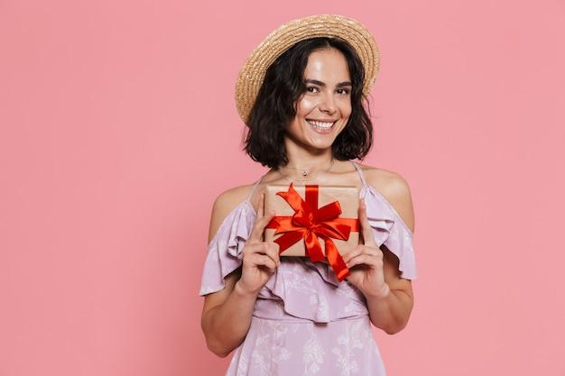 Afbeelding van een mooie jonge gelukkige vrouw poseren geïsoleerd over roze muur met huidige geschenkdoos.