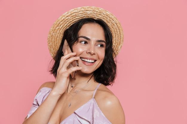 Afbeelding van een mooie jonge gelukkige vrouw poseren geïsoleerd over roze muur praten via de mobiele telefoon.