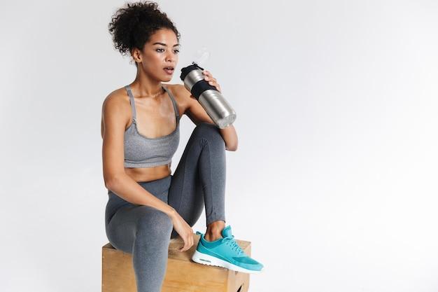 Afbeelding van een mooie jonge geweldige sport fitness afrikaanse vrouw drinkwater.