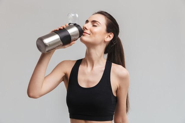 Afbeelding van een mooie jonge sport fitness vrouw drinkwater geïsoleerd over grijze muur.