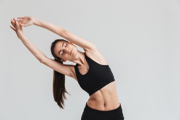 Afbeelding van een mooie jonge sport fitness vrouw maken oefeningen geïsoleerd over grijze muur.