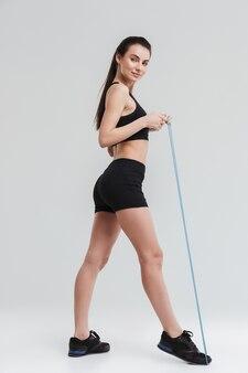 Afbeelding van een mooie jonge sport fitness vrouw maken oefeningen met apparatuur geïsoleerd over grijze muur.