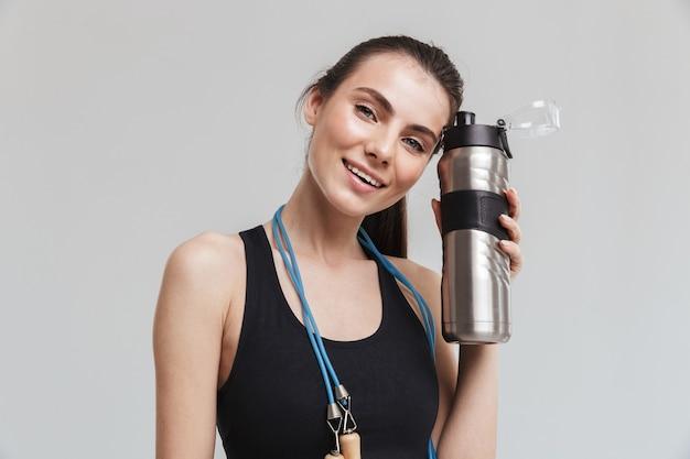 Afbeelding van een mooie jonge sport fitness vrouw poseren met springtouw geïsoleerd over grijze muur met fles met water.