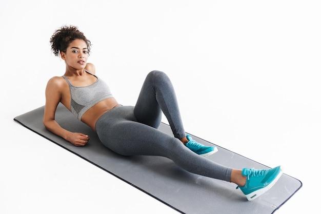 Afbeelding van een mooie jonge verbazingwekkende sterkere sportfitness afrikaanse vrouw maakt oefeningen geïsoleerd over een witte muurmuur.