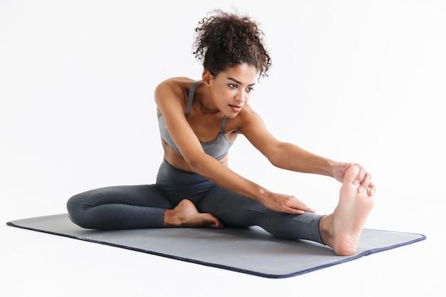 Afbeelding van een mooie jonge verbazingwekkende sterkere sportfitness afrikaanse vrouw maakt rekoefeningen geïsoleerd over een witte muurmuur.