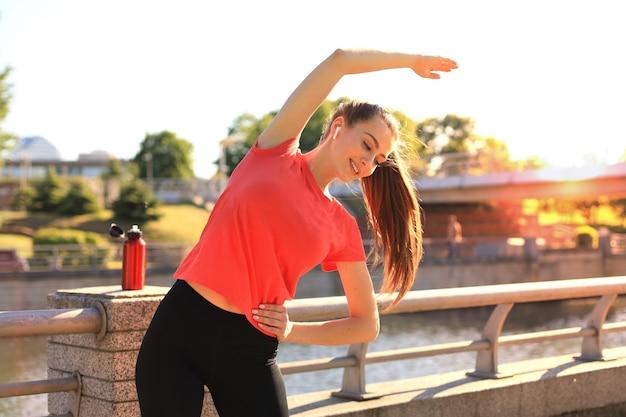 Afbeelding van een mooie jonge vrouw in sportieve kleding die haar lichaam uitrekt terwijl ze 's avonds traint in de buurt van de rivieroever van de stad.