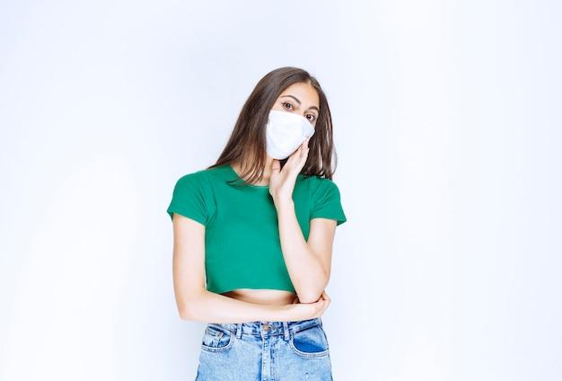Afbeelding van een mooie jonge vrouw met een medisch masker die naar de camera kijkt.