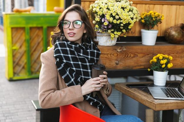 Afbeelding van een mooie jonge vrouw met laptopcomputer zitten in café buiten koffie drinken.