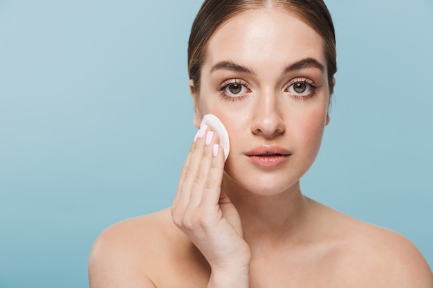 Afbeelding van een mooie jonge vrouw zorgt voor haar huid geïsoleerd over blauwe muur met wattenschijfje.