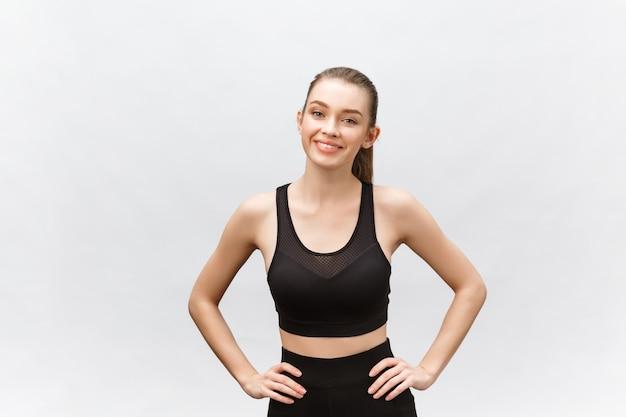 Afbeelding van een mooie sterke gelukkige vrolijke jonge sportvrouw poseren