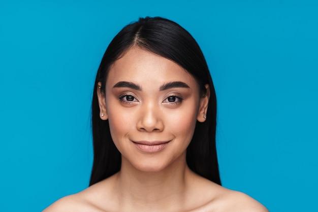 Afbeelding van een mooie tevreden positieve aziatische jonge vrouw poseren geïsoleerd op blauwe muur.