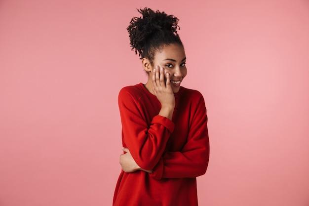 Afbeelding van een mooie verbazingwekkende jonge gelukkige opgewonden afrikaanse vrouw die zich voordeed op roze muurbekleding gezicht.