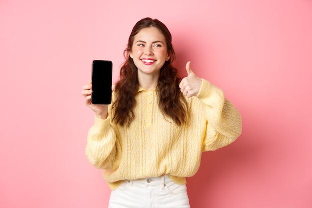 Afbeelding van een mooie vrouw die lacht en opzij kijkt terwijl ze een app beoordeelt met duimen omhoog en een leeg telefoonscherm die online promo aanbeveelt die tegen een roze muur staat