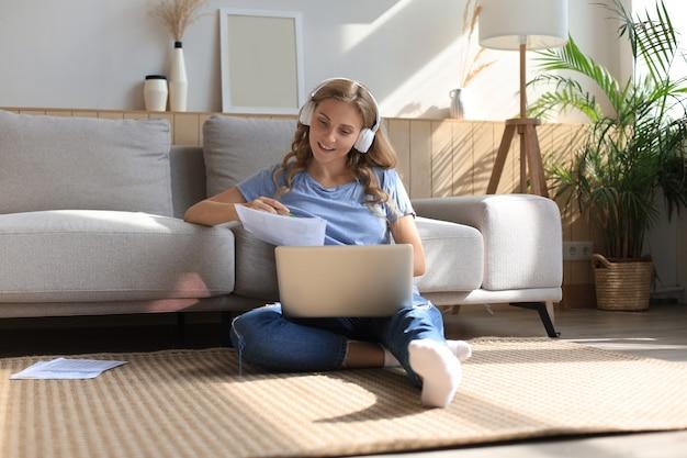 Afbeelding van een mooie vrouw die met een laptop werkt terwijl ze thuis op de vloer zit.