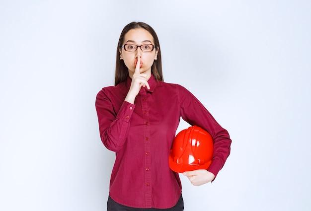 Afbeelding van een mooie vrouw in een bril die een crashhelm vasthoudt en een stil teken doet.