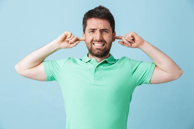 Afbeelding van een ontevreden jonge knappe bebaarde man die geïsoleerd over blauwe muurbedekkende oren poseert vanwege een luid.