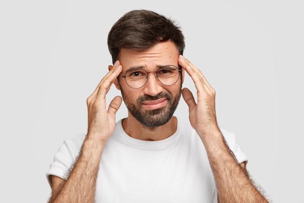 Afbeelding van een ontevreden man met een baard lijdt aan sterke hoofdpijn na een hele nacht werken, heeft een uitdrukking van vermoeidheid, houdt de handen op de slapen, fronst het gezicht, poseert tegen een witte muur. slecht gevoel
