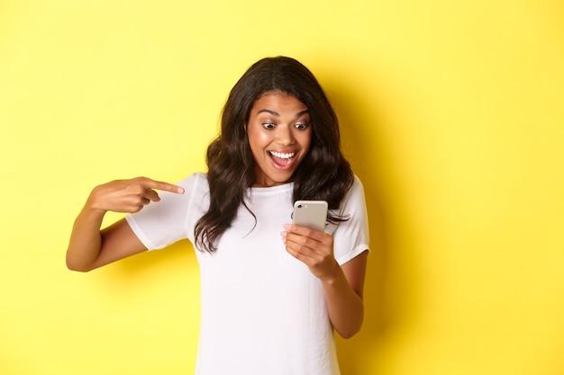 Afbeelding van een opgewonden afro-amerikaans meisje dat met de vinger naar de mobiele telefoon kijkt en iets ziet...