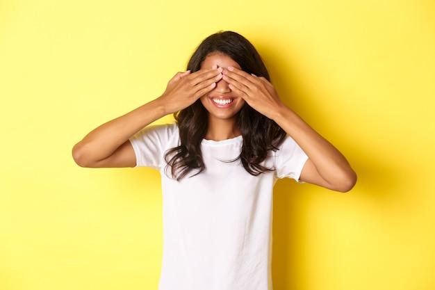 Afbeelding van een opgewonden afro-amerikaans meisje dat wacht op een verrassing die lacht en de ogen bedekt
