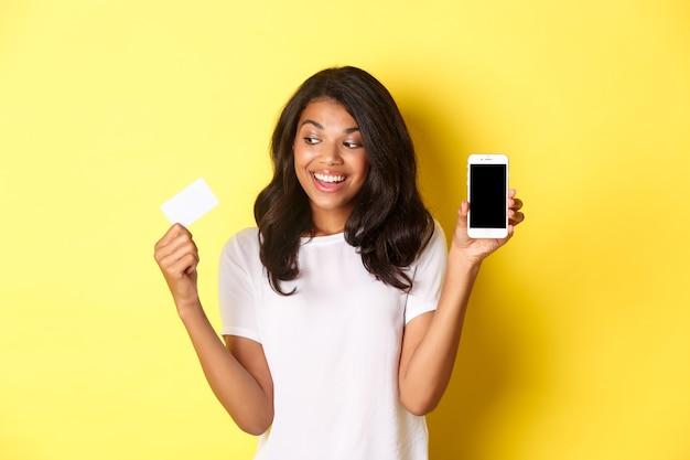 Afbeelding van een opgewonden afro-amerikaans vrouwelijk model met smartphonescherm en creditcard die boven...