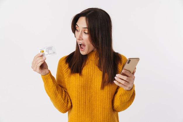 Afbeelding van een opgewonden brunette volwassen vrouw die een trui draagt met een mobiele telefoon en een creditcard op wit wordt geïsoleerd