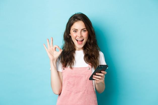 Afbeelding van een opgewonden en tevreden jonge vrouw die ja zegt na het gebruik van de smartphone-app, online winkelen met mobiele telefoon en het tonen van een ok-teken, staande op een blauwe achtergrond.